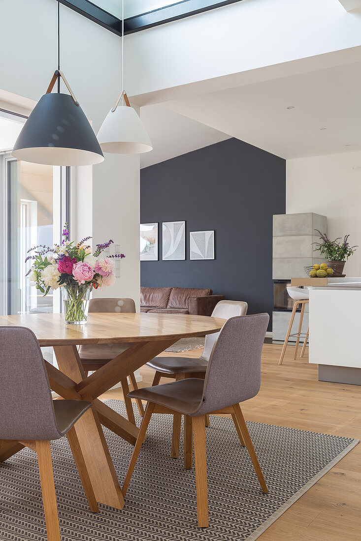 A round dining table with grey chairs in an open-plan living room