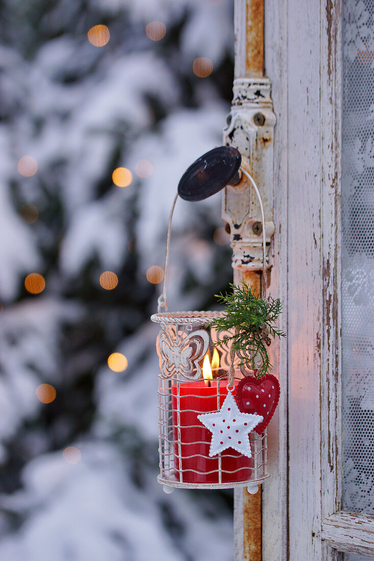 A Christmas lantern with a red candle hanging on a window