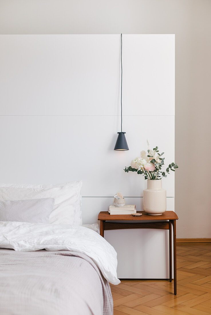 Bed, bedside table with flowers and pendant lamp in front of a white room divider