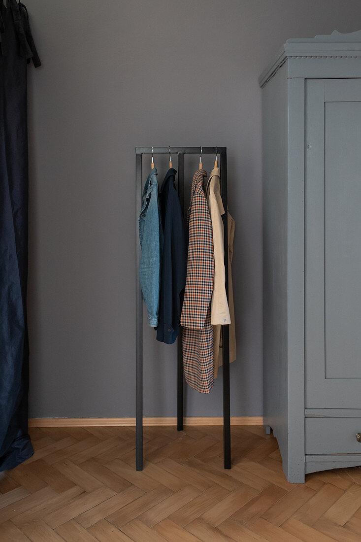 Clothes rack next to grey-blue wardrobe in hallway