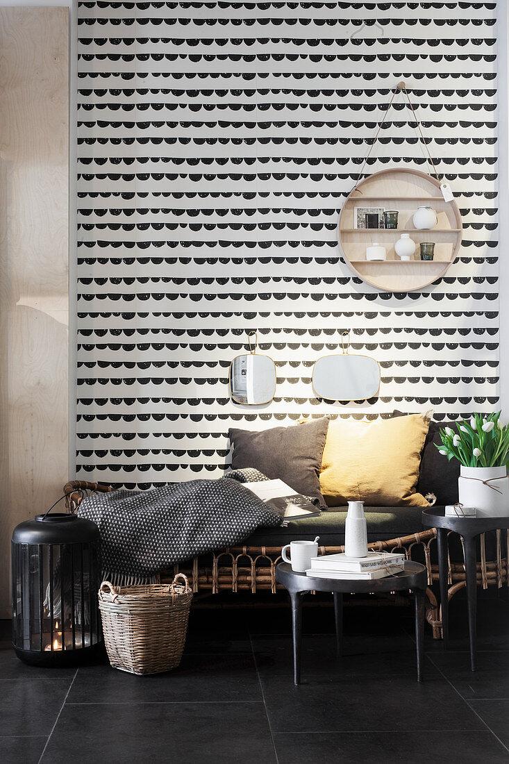 Rattan-Sitzbank mit Kissen vor Wandbehang