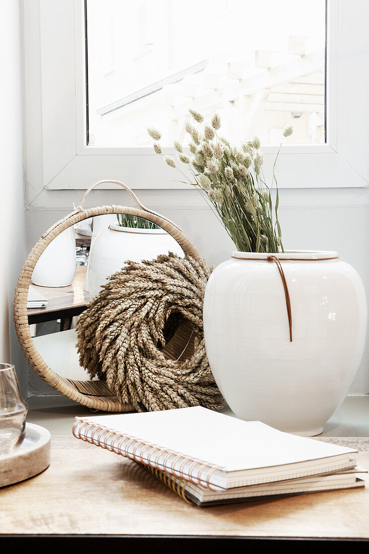 Vase with dried flowers, wreath, mirror and notebooks