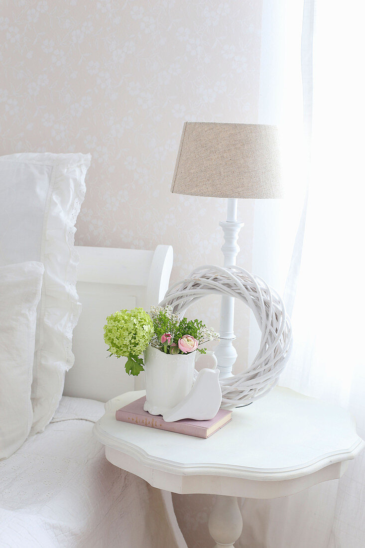 White wreath and spring flowers on bedside table next to bed