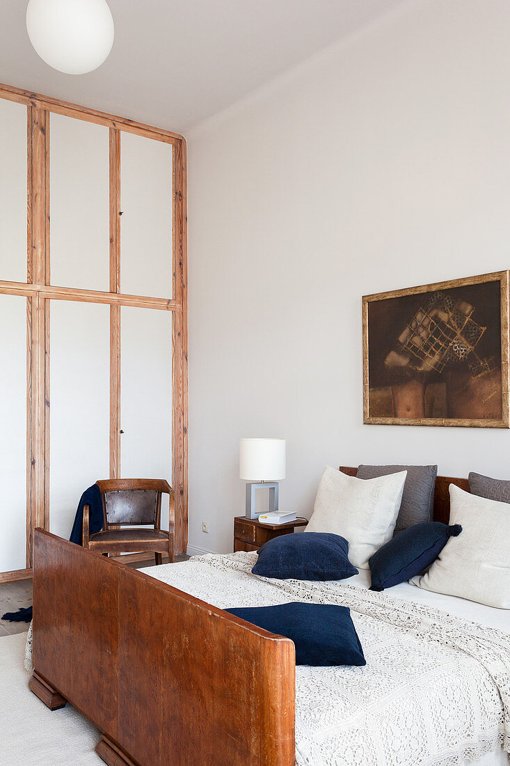 Double bed with wooden footboard in a high-ceilinged bedroom
