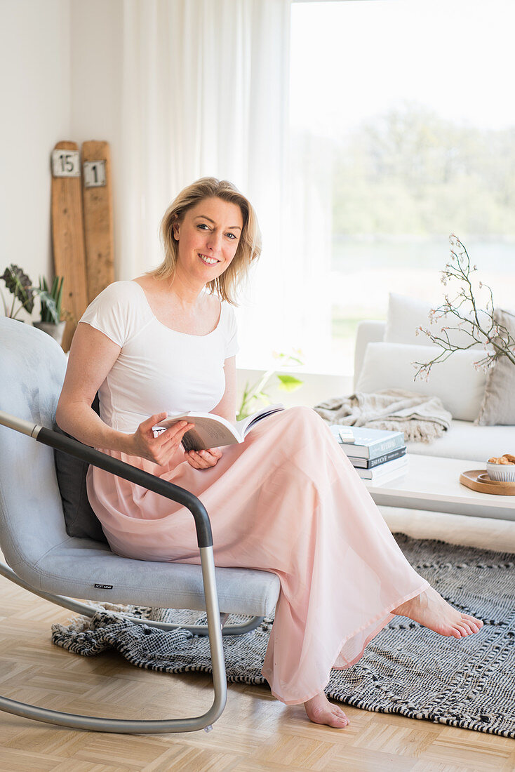 Blonde woman with book sitting in comfortable armchair