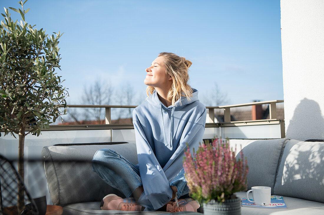 Blonde woman in casual wear sitting on the terrace