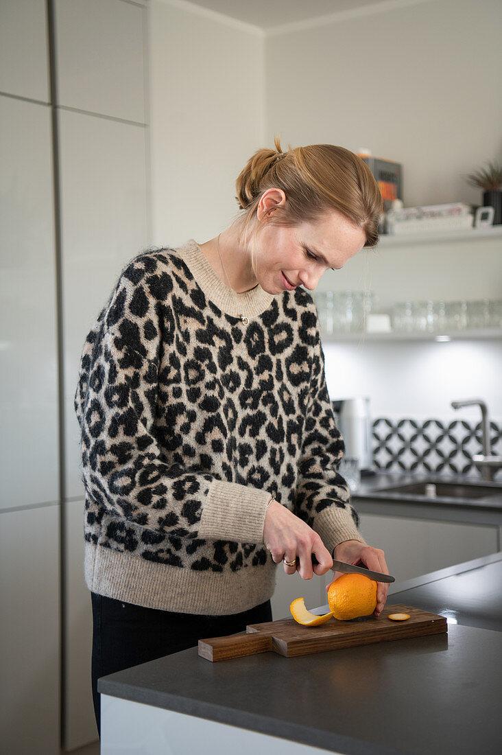 Blonde woman filleting an orange