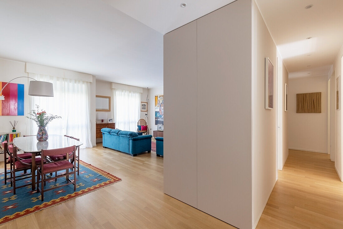 Open-plan interior with dining area, blue sofa in background and modular elements