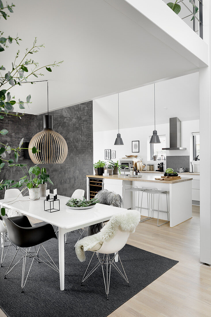 Dining table in modern, open-plan interior in grey and white