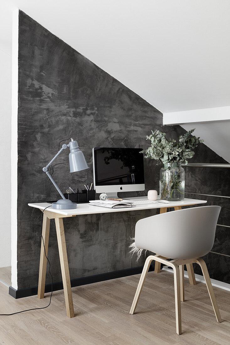 Scandinavian-style desk against grey wall below sloping ceiling