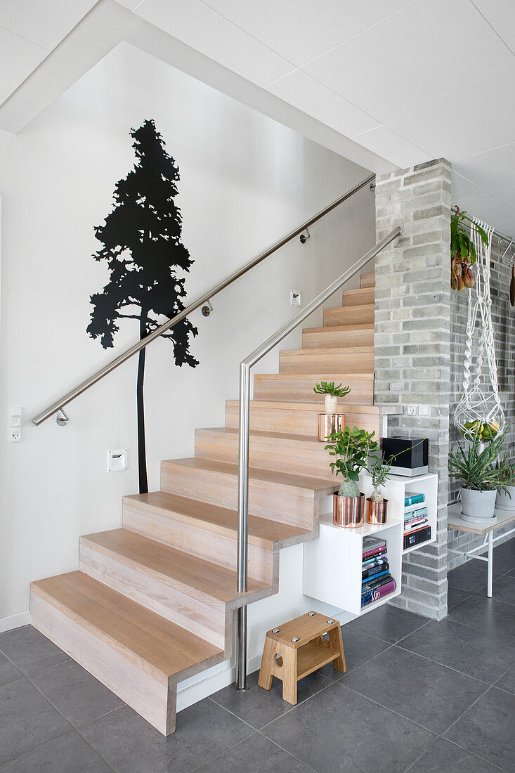 Wall decal with tree motif next to modern wooden stairs in hallway