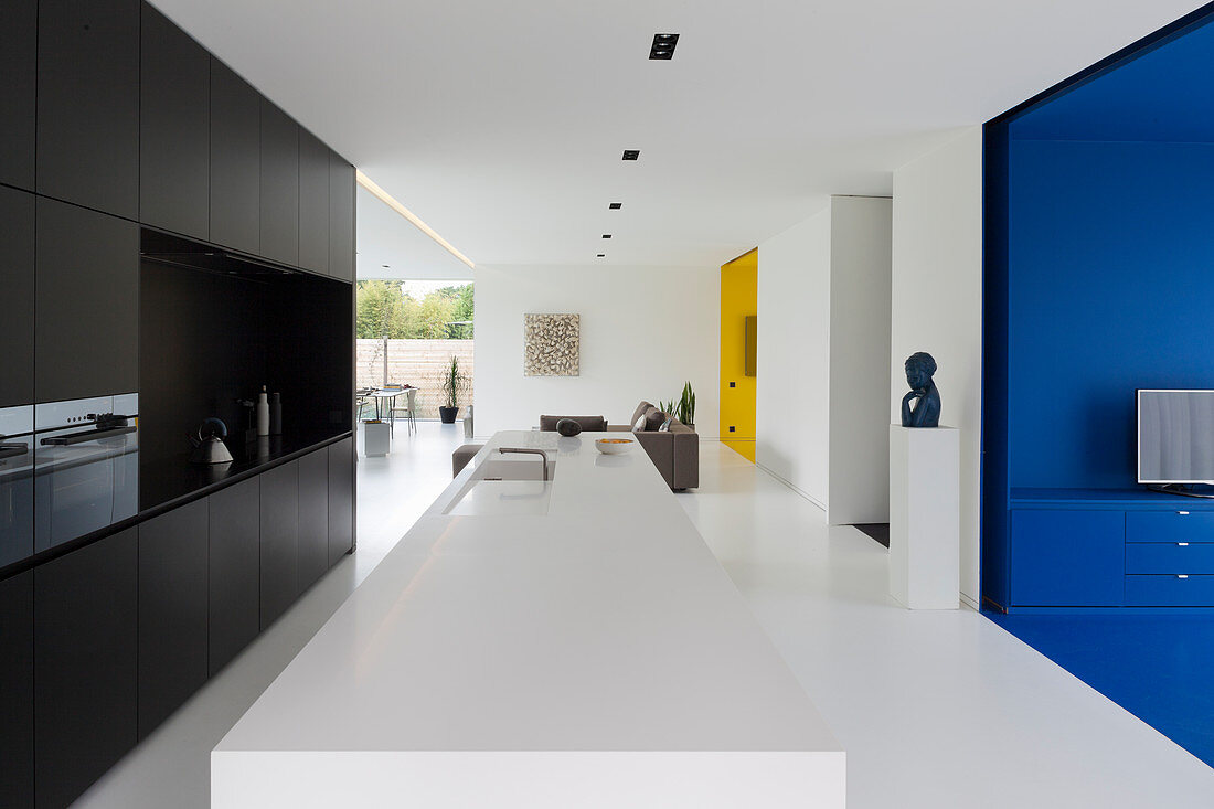 Modern kitchen in open-plan interior with brightly coloured alcoves