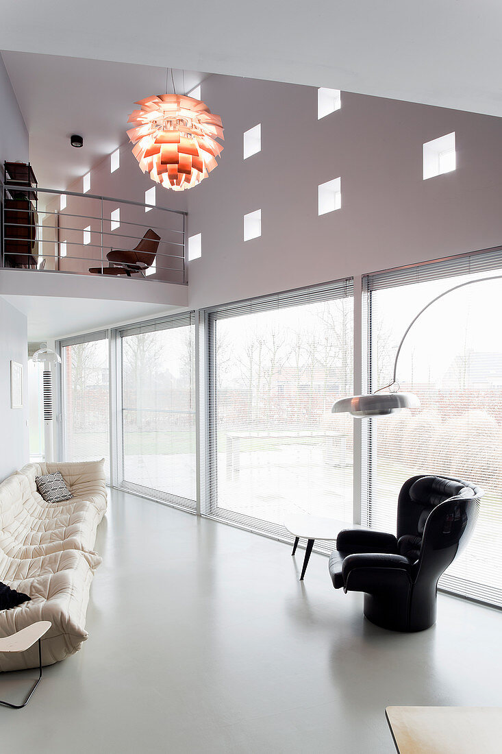 Row of large floor-level windows below wall with pattern of glass bricks in living room