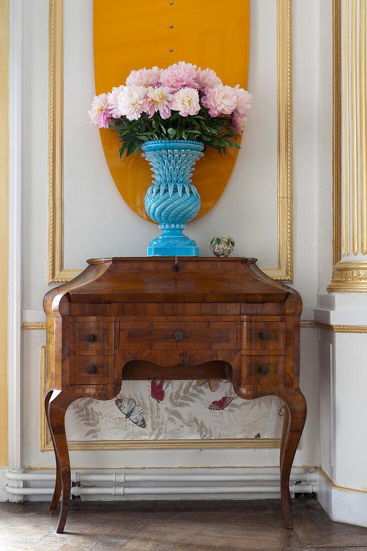Peonies in blue vase on old bureau against panelled wall