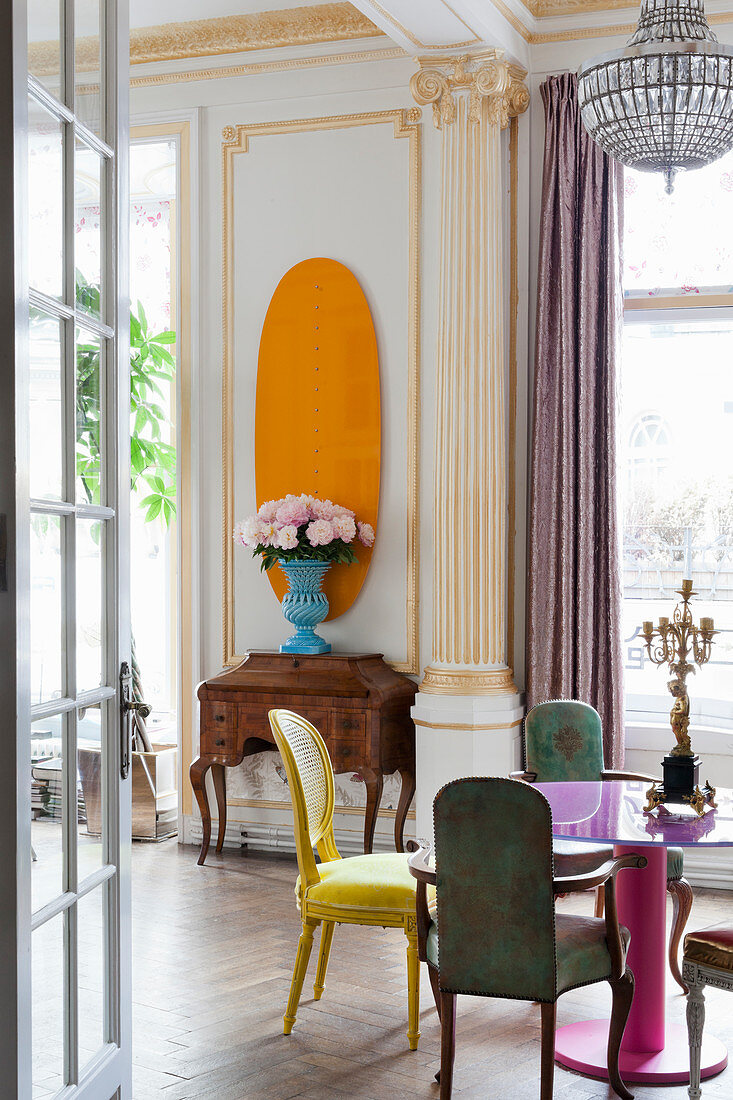 Colourful furniture and modern accents in classic living room with stucco elements