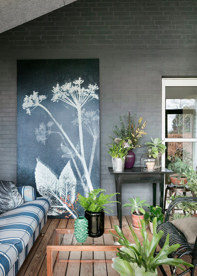 Picture of flowering umbellifer leaning against grey brick wall in living room