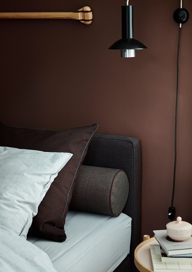 Bed with pillows and bolster against brown wall