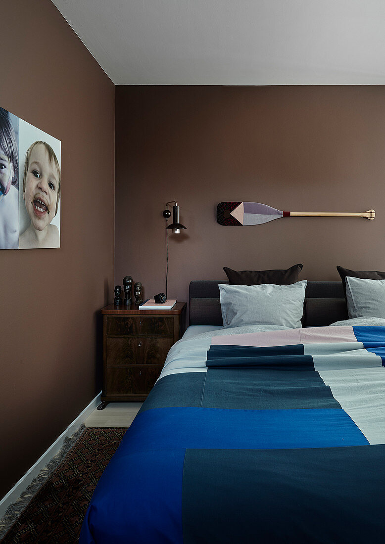 Double bed and bedside cabinet in bedroom with brown walls