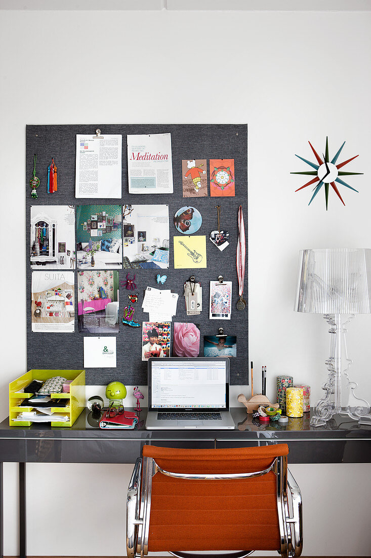Tidy pinboard above laptop on desk