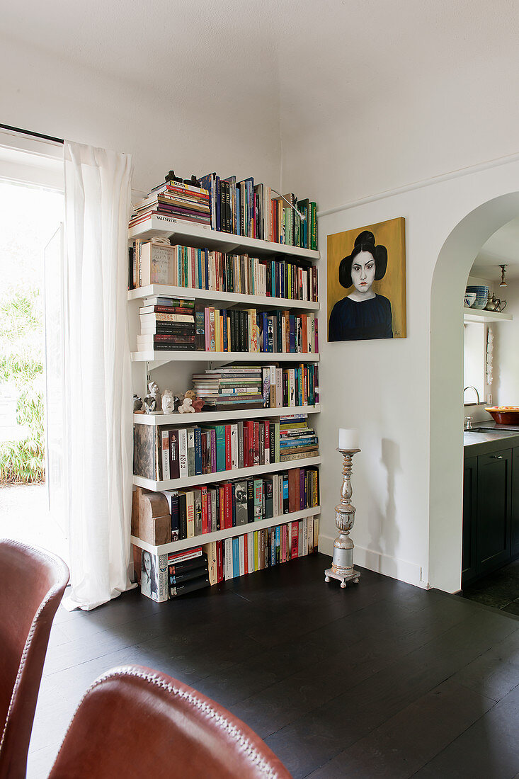 Book shelves, portrait and candlestick next to arched open doorway