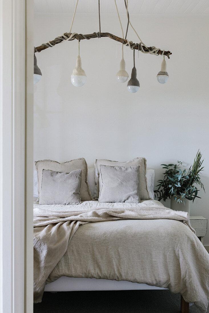 Pendelleuchten an einem Ast über dem Bett im schlichten Schlafzimmer