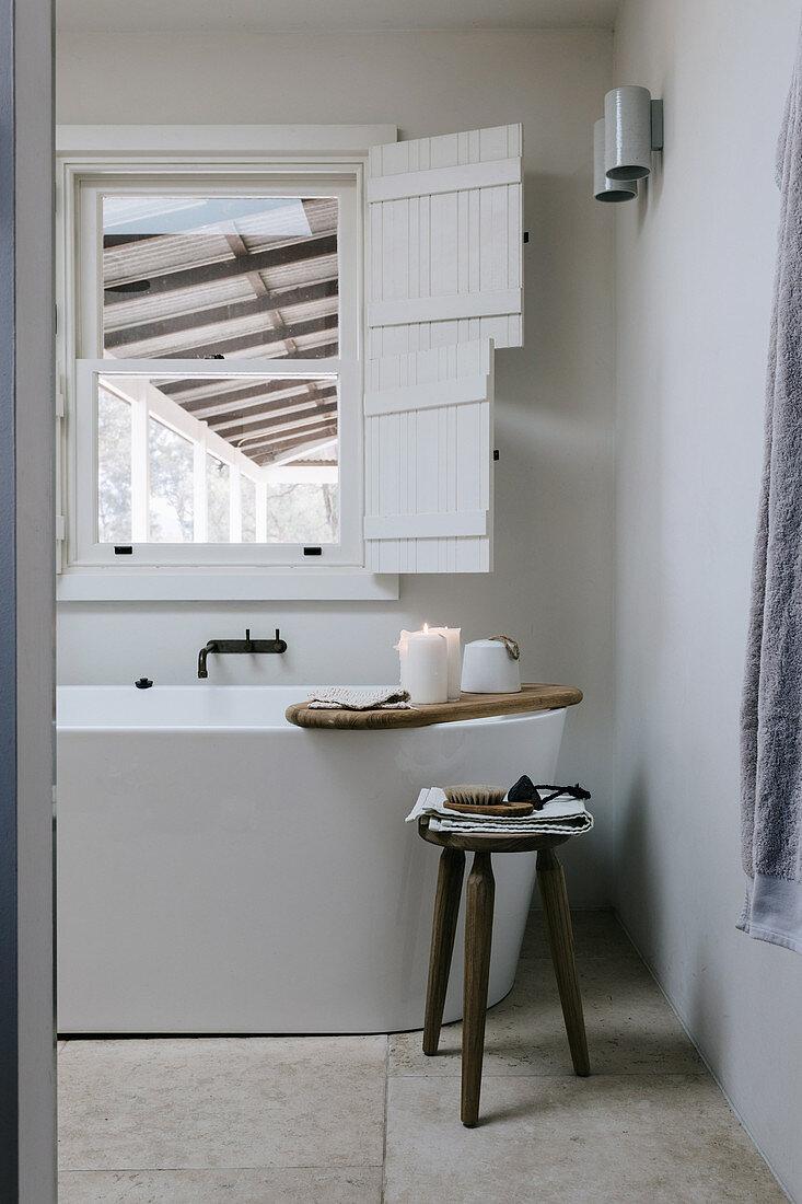Freistehende Badewanne unterm Fenster mit Fensterläden im Bad