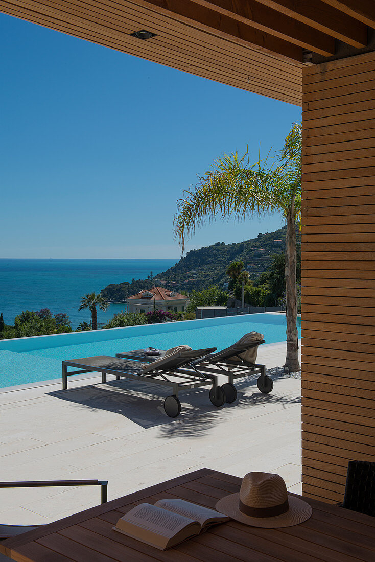 View of swimming pool and sea from roofed terrace