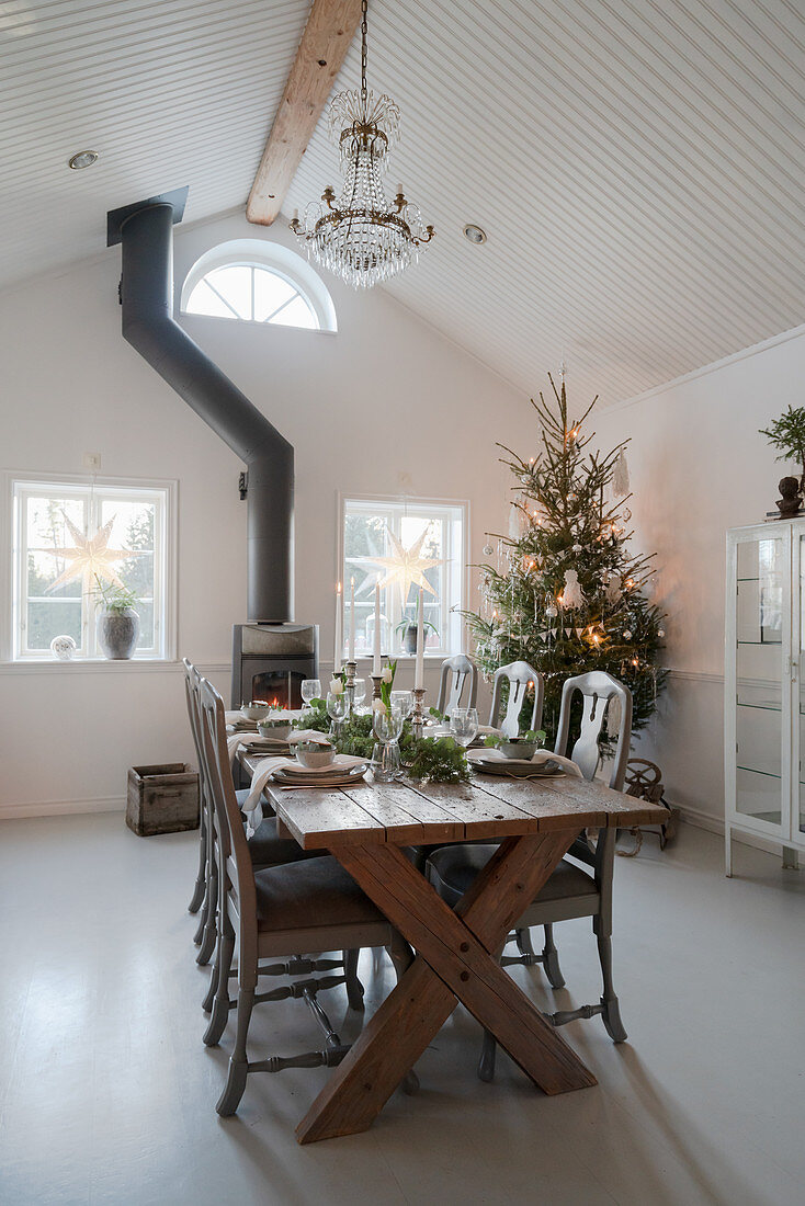Festively set wooden table in dining room with high ceiling