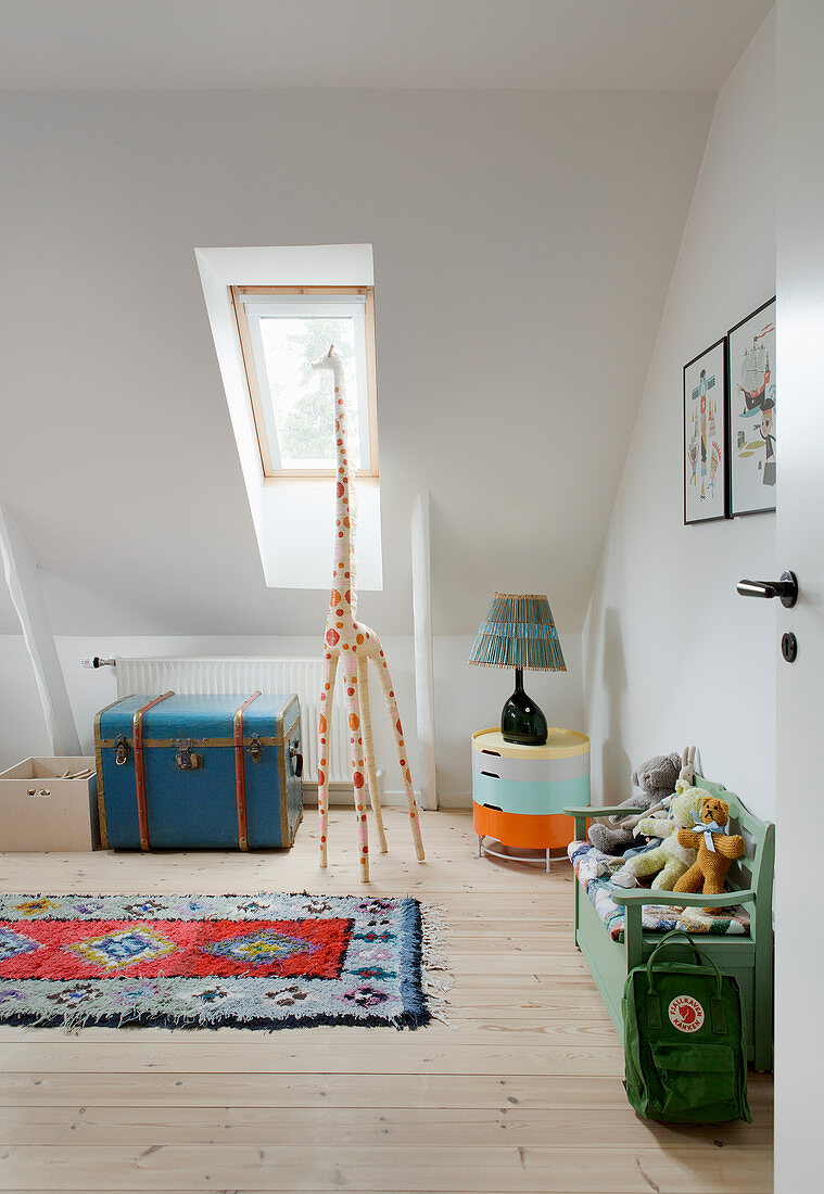 Giraffe and flea-market furniture in child's bedroom with sloping ceiling