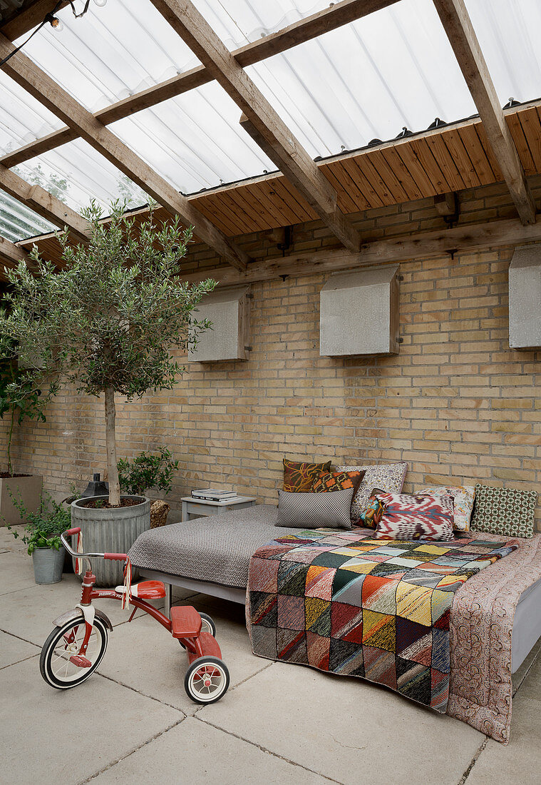 Tricycle, sofa and olive tree in conservatory with brick walls
