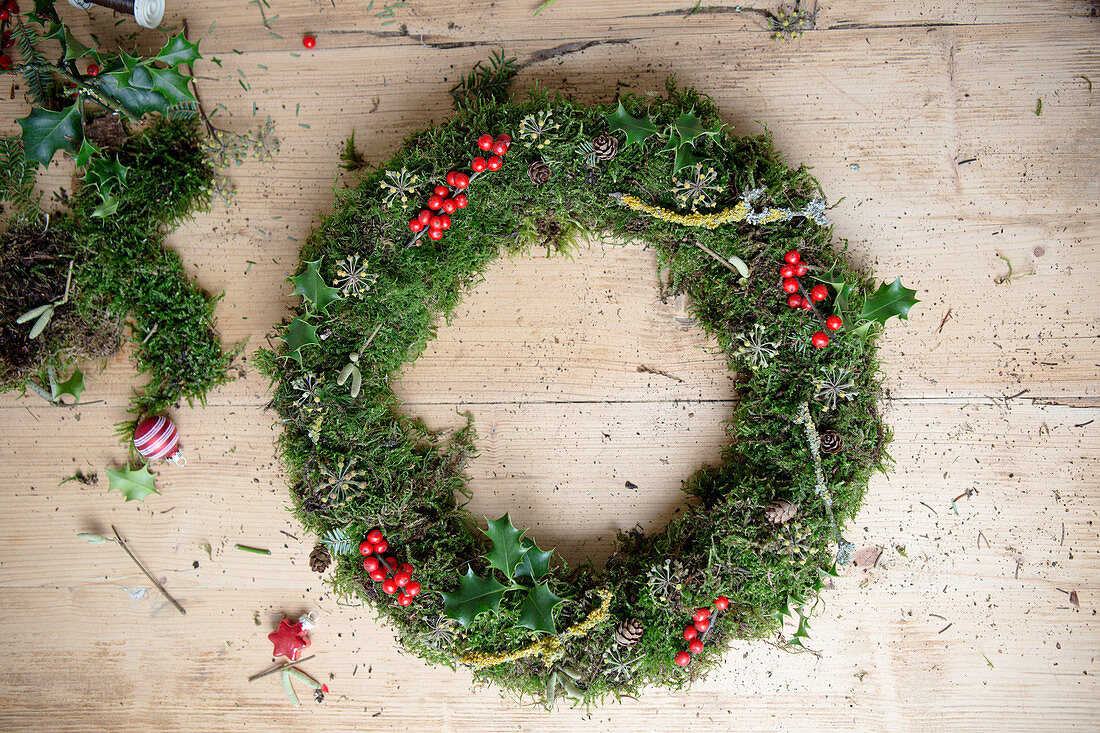 Handmade moss wreath with holly berries, twigs and pine cones