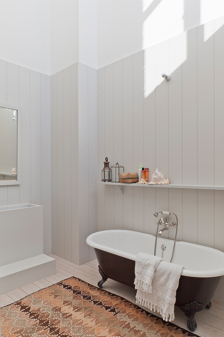 Free-standing bathtub against pale wooden cladding in bathroom