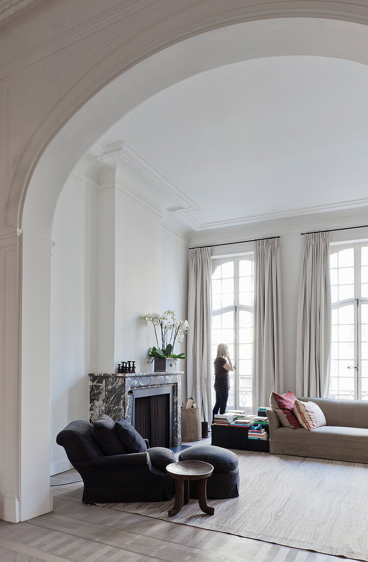View of armchair and fireplace in living room seen through arched open doorway