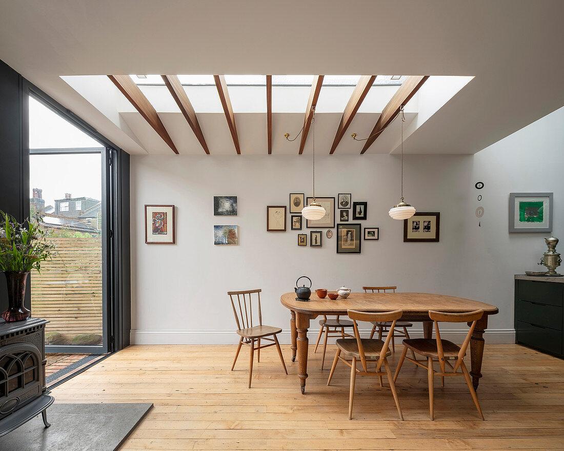 Old dining table below skylight next to open terrace doors