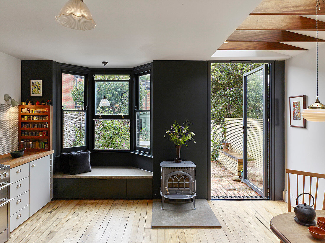 Classic kitchen-dining room with seat in bay window and door leading into garden