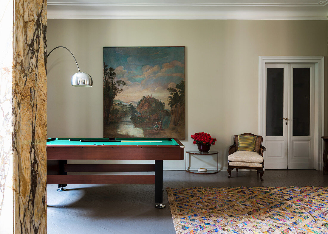 Billiard table, armchair and side table next to painting on wall
