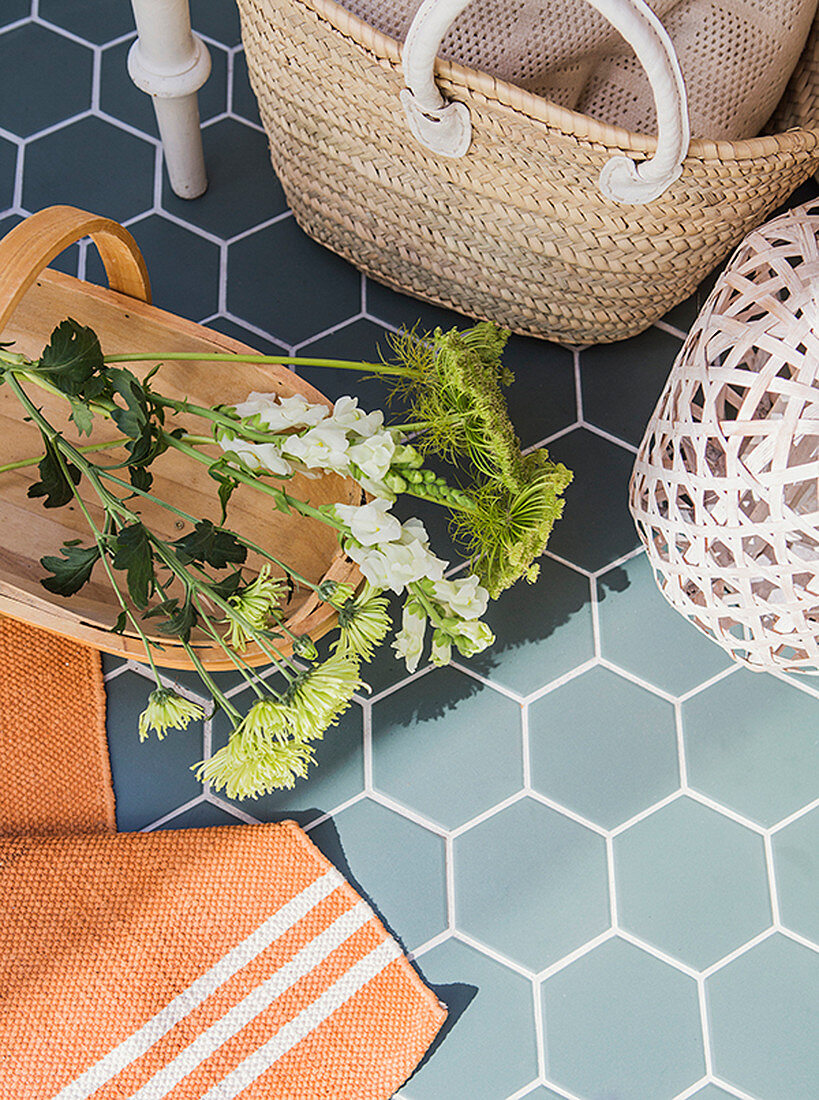 Flowers in wooden trug and raffia basket on tiled floor