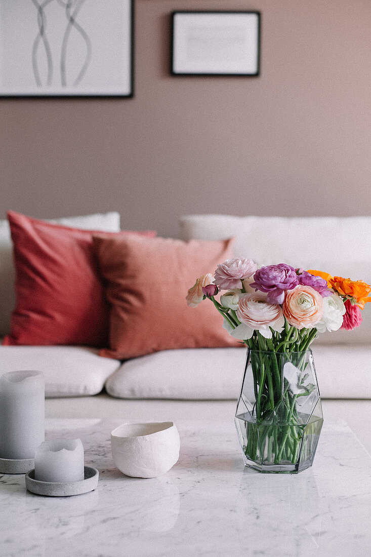 Glass vase of ranunculus, bowls and candles in coffee table