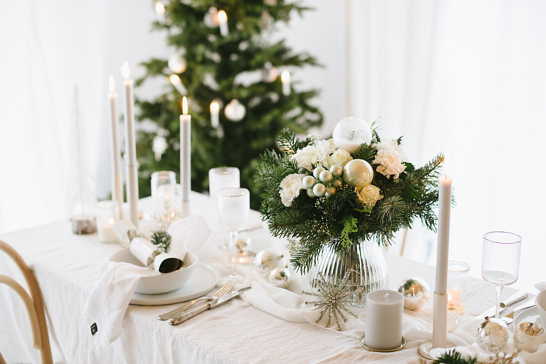 Flowers and gifts on table set for Christmas in shades of cream
