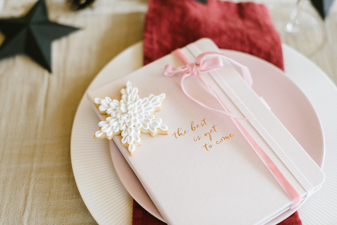 Christmas place setting with party favour and snowflake-shaped biscuit
