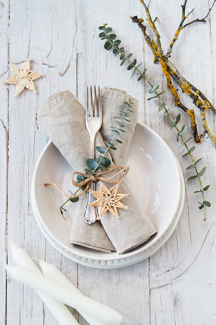 Festive place setting decorated with eucalyptus, straw stars and natural materials