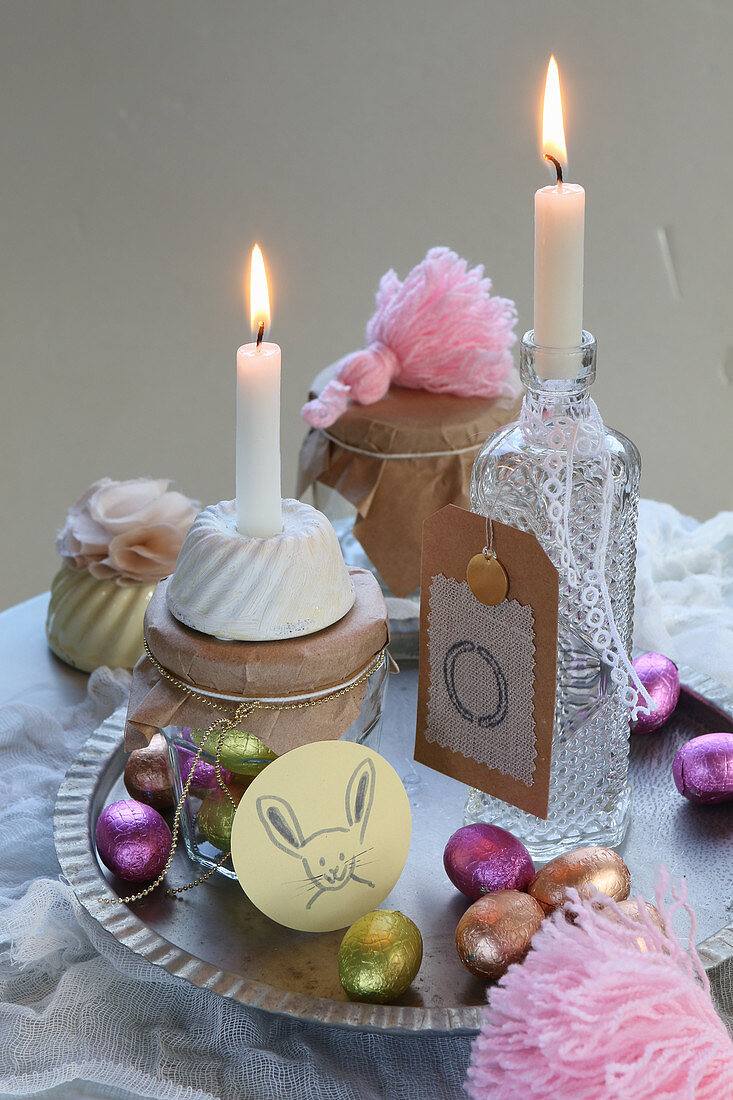 Vintage arrangement of candles and chocolate Easter eggs on table