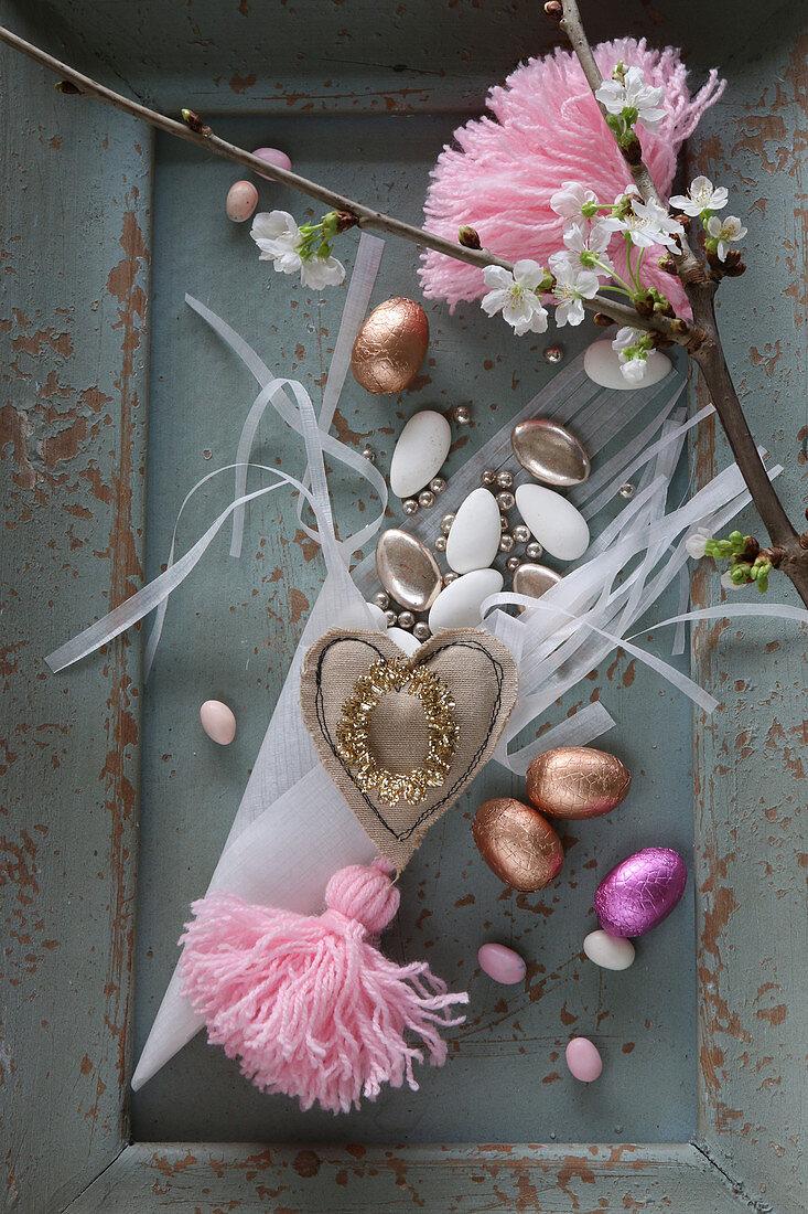 Romantische Osterdeko mit Schokoeiern und rosafarbenen Quasten