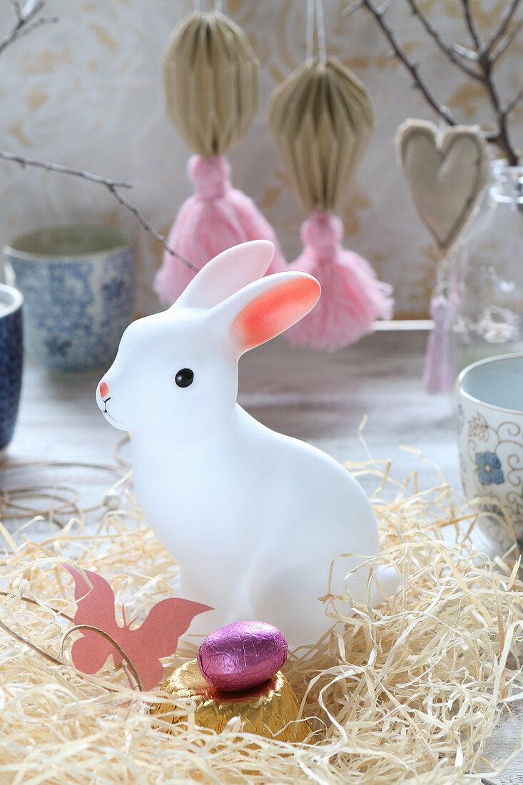 Weiße Hasenfigur im Nest aus Holzwolle als Osterdeko