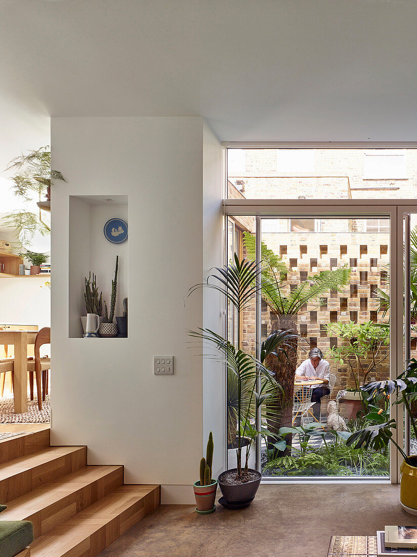 Open glass sliding doors leading to small courtyard garden with foliage plants