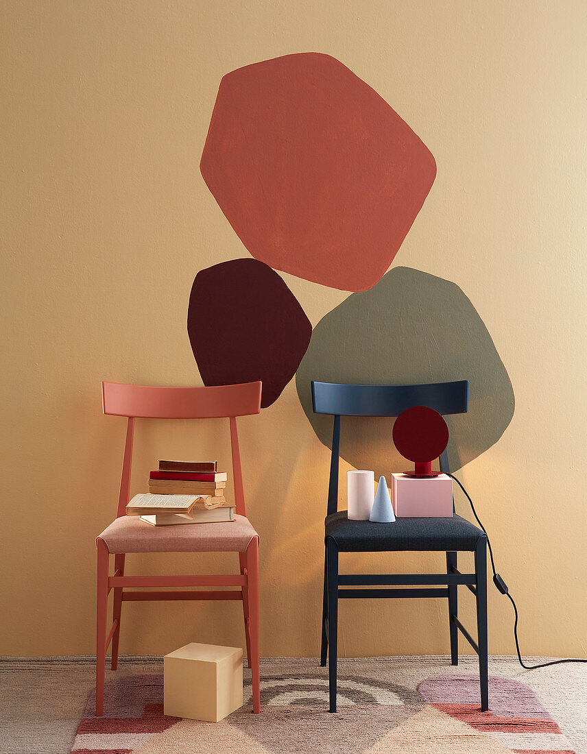 Two chairs in front of patches of colour on wall in warm shades