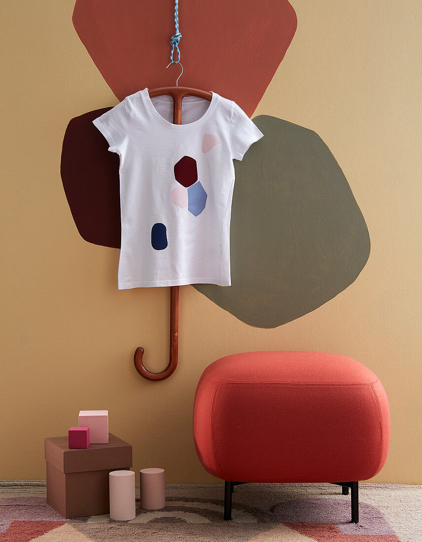 Painted T shirt and pouffe against wall with patches of colour