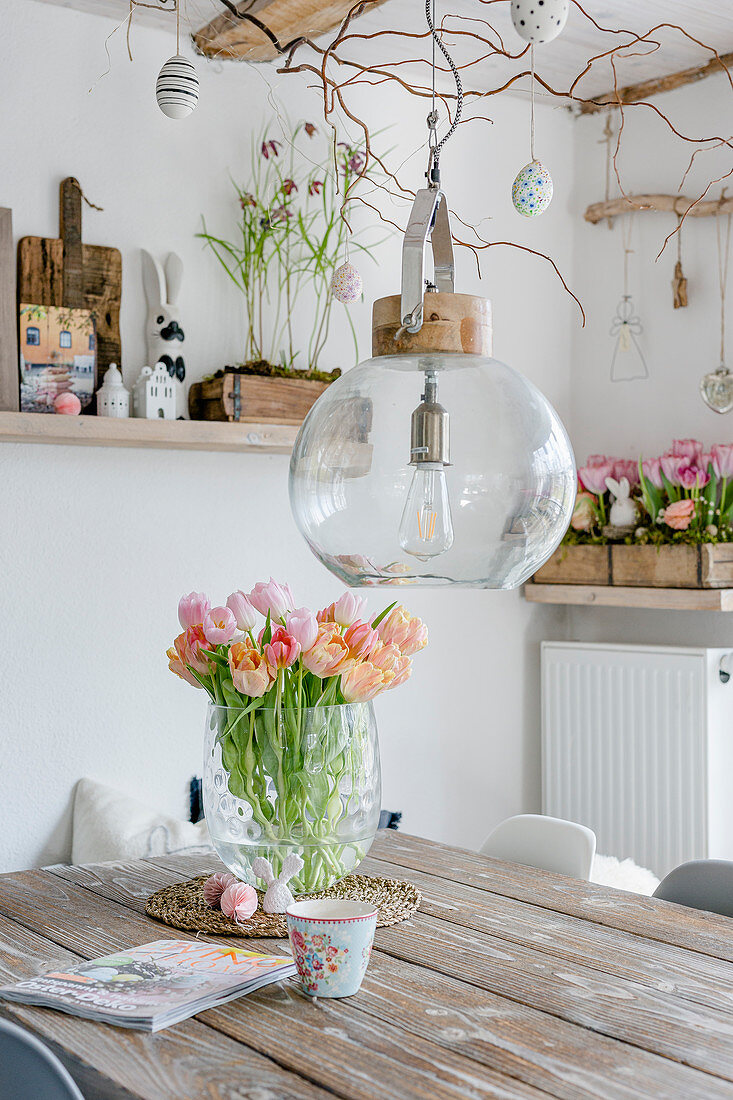 Vase of tulips on table in dining room with rustic spring decorations