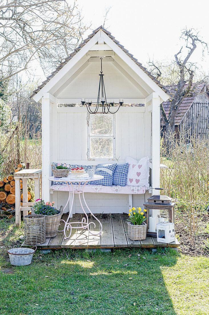 Romantische Kissen auf der Bank in der Gartenlaube mit kleiner Terrasse