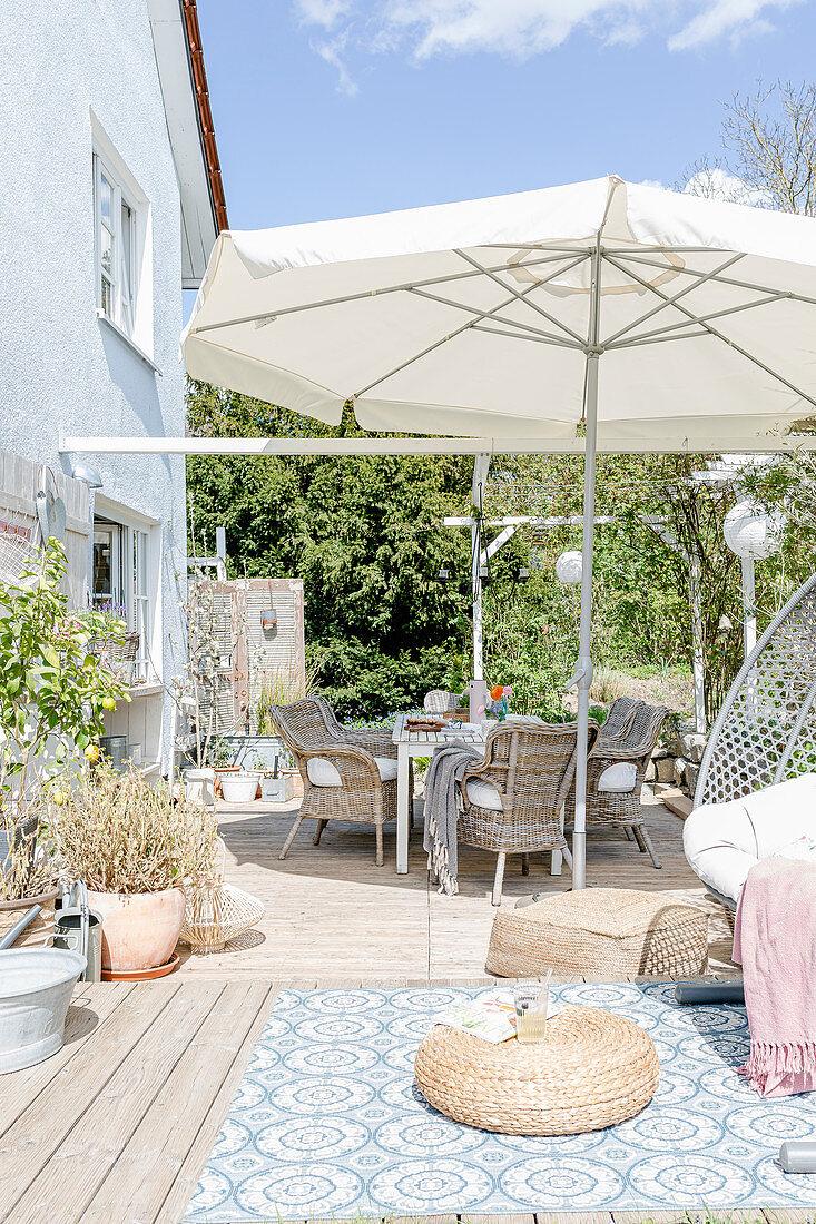 Rattan armchairs below parasol on terrace in spring